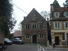 Stone building with arched doorway on ground floor. Three windows on first floor and single window below roof level. To the left are trees and cars, to the right another building.