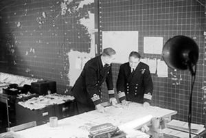 Commander-in-Chief, Western Approaches - Commander RDS Crosse, Staff Officer Convoys, (left) discussing a special convoy movement map with Captain Lake, RN, Duty Officer in the Operations Room at Derby House, Liverpool.