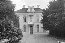 """Elegancki biały dwukondygnacyjny dom o europejskim wyglądzie z napisem """"ORANJELUST"""" nad drzwiami."""