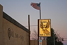 "The text ""Owl Bar and Cafe"" on the building, with an illuminated sign saying the same, with a graphic of an owl."
