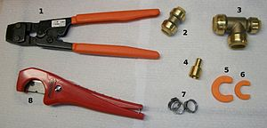 English: Tools and fittings used in a plumbing...