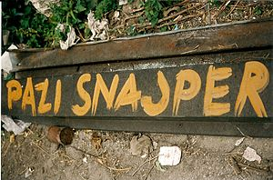 "Sniper Alley - Hand-painted warning sign: ""Watch out – Sniper!"""