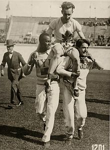 "A man is carried on the shoulders of two other men. He is in a white shirt and shorts with a stylized maple leaf logo above the letters ""CAN"", while the two men carrying him, one black the other white, are in white long-sleeve shirts and full-length track pants"