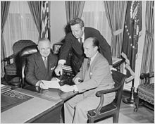 Three men at a desk reviewing a document