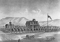 A black-and-white illustration showing the house on a large block surrounded by small trees, with a horse-drawn vehicle in front, large flag on a pole to the right, and mountains in the background