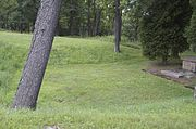A patch of mowed grass that is indented into the ground.