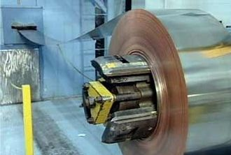 Planchet - A 6,000-pound coil is fed into a blanking press at the US Mint.