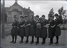 "Eight women in dresses stand in a line on a patch of dirt in front of Holmes Hall; one in the center holds a basketball with ""'03"" written on it"