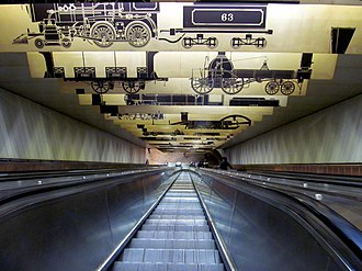 Porter station - Looking down the MBTA's longest escalator, at Porter station. This escalator runs from the fare mezzanine to the inbound subway platform level. The overhead graphics theme commemorates early railroad history.
