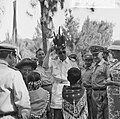 Prins Bernhard terwijl hij een Indiaanse hoofdtooi op zet koningin Juliana (l.), Bestanddeelnr 918-3322.jpg