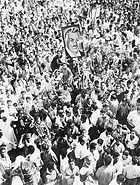 A crowd of people, many waving. One person is holding up a portrait of a man