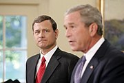 John Roberts appears in the background, while President Bush is announcing his nomination for the position of Chief Justice.