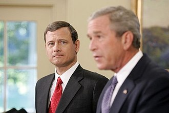 John Roberts - John Roberts appears in the background, as President Bush announces his nomination of Roberts for the position of Chief Justice.