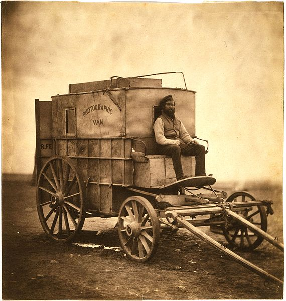 Roger Fenton's assistant seated on Fenton's photographic van, Crimea, 1855.