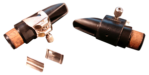 Ligature (instrument) - Two clarinet mouthpieces with ligatures. On the left, a silver Vandoren Optimum ligature (with interchangeable pressure plates), and on the right, a naugahyde Rovner wrap-around ligature. Both are displayed without reeds.