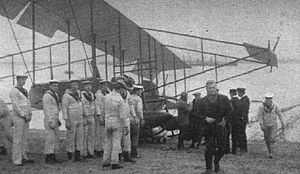 """Arthur Longmore - Then-Lieutenant Arthur Longmore (in dark coat walking toward camera on right) on 1 December 1911 immediately after he became the first person in the United Kingdom to take off from land and make a successful water landing, using the aircraft behind him, a Short Improved S.27 bearing Admiralty number 38, later often called the """"Short S.38."""""""