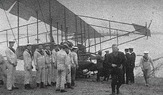 "Arthur Longmore - Then-Lieutenant Arthur Longmore (in dark coat walking toward camera on right) on 1 December 1911 immediately after he became the first person in the United Kingdom to take off from land and make a successful water landing, using the aircraft behind him, a Short Improved S.27 bearing Admiralty number 38, later often called the ""Short S.38."""