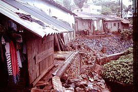 Slums-of-Mumbai-1979-Corrugated-iron-roofs-slope-with-stones-IHS-87-06.jpeg