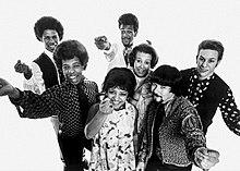 Sete jovens adultos com roupas e cabelos extravagantes.