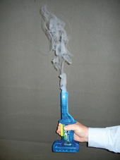 A hand grasping a small blue apparatus with white smoke emerging from its top