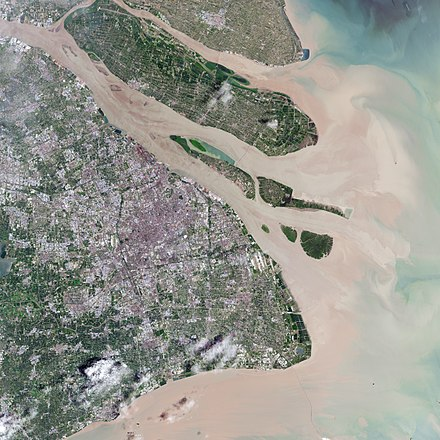 This natural-color satellite image shows the urban area of Shanghai in 2016, along with its major islands of (from northwest to southeast) Chongming, Changxing, Hengsha, and the Jiuduansha shoals off Pudong. Yangtze's natural sediment discharging can be seen. Sprawling Shanghai 2016-07-20.jpg
