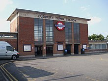 "A box-like red-brick building with a projecting flat concrete roof and concrete band below. Four vertical glazed panels in two pairs divide the front elevation. In the centre is the Underground roundel of a red ring with a blue bar and the word ""UNDERGROUND"". ""SUDBURY TOWN STATION"" is in lettering fixed to the concrete band beneath the roof."