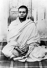 Vivekananda siedzi, ubrany w biały szal