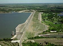 From the west, a large dam and the body of water it holds sit to the left of a grassy area with some trees