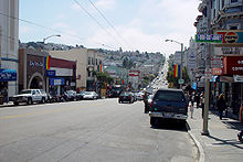 A street extending into the background. Stores line both sides of the street, and many light poles carry rainbow flags.