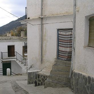 Alpujarras - A street corner in Trevélez showing traditional architecture and door curtain