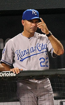"A man wearing a blue baseball cap with the letters ""KC"" gestures with his hands."