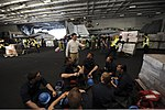 U.S. Navy Cmdr. Mark Escoe, in white shirt, the supply officer aboard the aircraft carrier USS Nimitz (CVN 68), briefs a group of midshipmen on the logistics involved in an underway replenishment in 130622-N-TX484-029.jpg