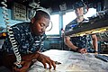 U.S. Navy Quartermaster 3rd Class Juan Burns, left, assigned to the guided missile cruiser USS Antietam (CG 54), reviews navigational charts in the bridge wing as the ship prepares to leave Hong Kong Nov. 12 131112-N-TG831-184.jpg