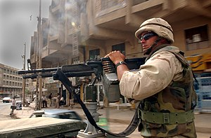 Triangle of Death (Iraq) - A U.S. Navy Seabee mans a vehicle-mounted machine gun while travelling through Al Hillah, Iraq in May 2003.