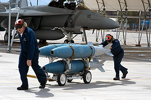 US Navy 040329-N-7191C-001 Aviation Ordnanceman assigned to the Black Knights of Strike Fighter Squadron One Five Four (VFA-154) transport a full skid of MK-83 general purpose, 1,000 pound inert practice bombs.jpg
