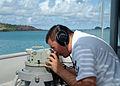 US Navy 060527-N-4124C-018 Quartermaster 2nd Class Maynard Sagaya takes bearings reading aboard the Avenger-class mine warfare ship USS Patriot (MCM 7).jpg