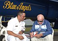 US Navy 061027-N-1810F-039 Raleigh Dusty Rhodes, one of the first pilots and commanders of the Blue Angels, autographs a poster for Mass Communication Specialist 2nd Class Joseph Olivares before the practice air show aboard Nav.jpg