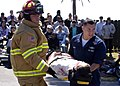 US Navy 070404-N-9132D-005 Aviation Boatswain Mate (Handling) 2nd Class Russel Armand and Hospital Corpsman 2nd Class Dan Gomez carry a crash victim from the scene of a mock accident during the Day of the Dead.jpg