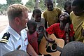 US Navy 070908-N-3255B-004 Lt. Dave Evans, assistant director of the U.S. Navy Europe-Africa Band, Topside, gives a guitar lesson to children at the Yatima Group Orphanage.jpg