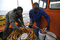 US Navy 090329-N-5242D-120 Navy Diver 2nd Class Ellex Sturkey and Uganda Peoples' Defence Air Force Lt. Robert Kijjali put away gear after one of Sturkey's colleagues completes a dive into Africa's Lake Victoria.jpg