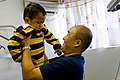 US Navy 090715-N-9689V-002 Cmdr. Joseph Yang, Pacific Partnership 2009 contingency dental officer-in-charge, lifts a child from a dental chair after a dental surgery during a medical civic action project at Niu'ui Hospital.jpg