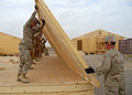 US Navy 090916-N-9564W-012 Seabees assigned to Naval Mobile Construction Battalion (NMCB) 74 raise a wall panel for a Southwest Asia hut.jpg
