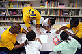 US Navy 091029-N-6220J-005 Aviation Boatswain's Mate (Fuels) 1st Class Ulric Carter, left, Boatswain's Mate 2nd Class Terrence Phillips and Operations Specialist 2nd Class Shevete Johnson help tutor students with their homework.jpg