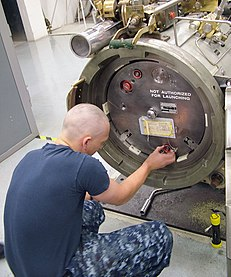 US Navy 091112-N-9531K-004 Fireman Recruit Patrick Todd, a student at Basic Enlisted Submarine School, uses the Torpedo Tube Trainer to learn how to load Tomahawk cruise missile.jpg