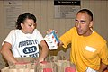 US Navy 100217-N-8020M-039 Navy Counselor 1st Class Nicolas Carbajal loads bags of food with a prospective recruit at St. Mary's Food Bank.jpg
