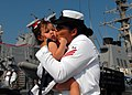 US Navy 100901-N-5292M-106 Damage Control Fireman Anhay Tetreault kisses her daughter during a homecoming celebration for the guided-missile destroyer USS Cole (DDG 67).jpg