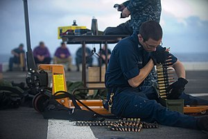 US Navy 111229-N-PB383-138 Gunner's Mate 3rd Class Joshua Velchansky organizes .50-caliber machine gun ammunition during a live-fire exercise aboar.jpg