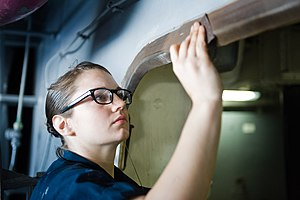 US Navy 120101-N-RJ456-012 Seaman Shelby Eby, from Lewisburg, Ohio, performs corrosion prevention on a hatch aboard the Nimitz-class aircraft carri.jpg