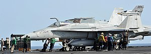 US Navy 120216-N-KQ416-247 Sailors push an F-A-18C Hornet assigned to the Vigilantes of Strike Fighter Squadron (VFA) 151 into position on the flig.jpg