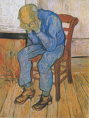 An old man with a bald head is sitting on a yellow chair by his fire. There is a low fire in the grate, he is dressed in blue clothes. He is holding his head in his hands.